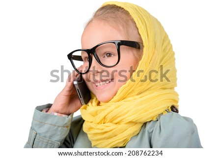 Portrait of a little fashion girl in coat, scarf, sunglasses, talking on the phone, on a white background - stock photo