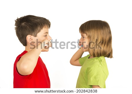Portrait of a little girl and a young boy brushing teeth facing each other  - stock photo