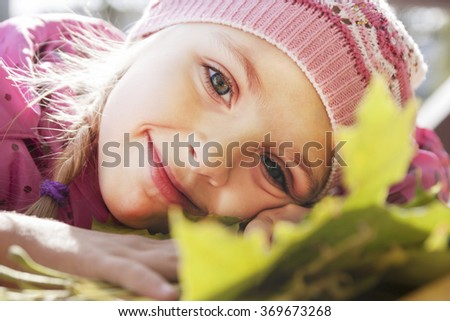 portrait of a little girl and autumn leaves - stock photo