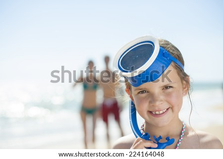 portrait of a little girl at the beach with a diving mask with his parents in the background - stock photo