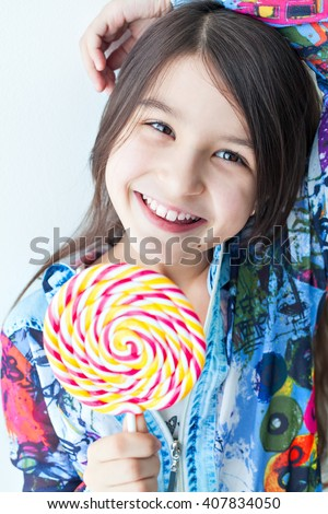 Portrait of a little girl child fashion. Stylish little girl with long hair with candy in hand, posing looking at the camera. Photo model child cool fashionable. Carefree fun - stock photo