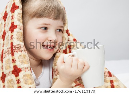 Portrait of a little girl covering with a rug and holding a white cup - stock photo