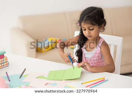 Portrait of a little girl cutting a paper - stock photo