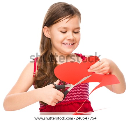 Portrait of a little girl cutting out red heart, isolated over white - stock photo