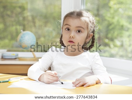 Portrait of a little girl drawing with pencils, looking at camera  - stock photo