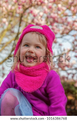 portrait of a little girl during spring with a blooming magnolia tree in the background