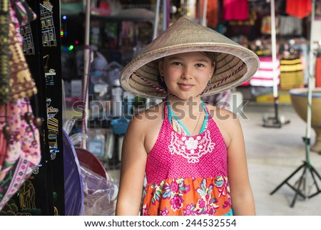 Portrait of a little girl from Europe in the Vietnamese hat - stock photo