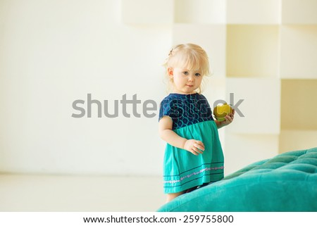 portrait of a little girl holding an apple in his hand - stock photo