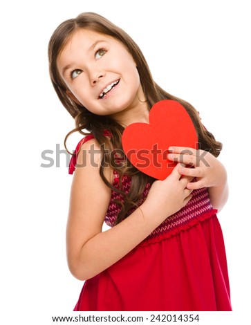 Portrait of a little girl holding red heart and daydreaming, isolated over white - stock photo