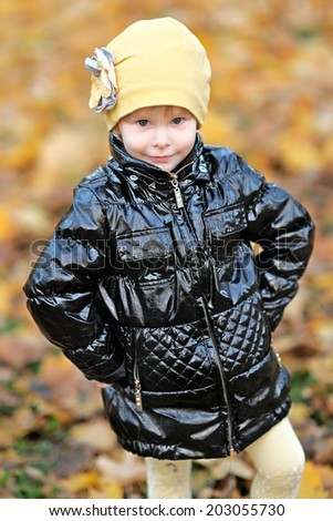 portrait of a little girl in a park in autumn - stock photo