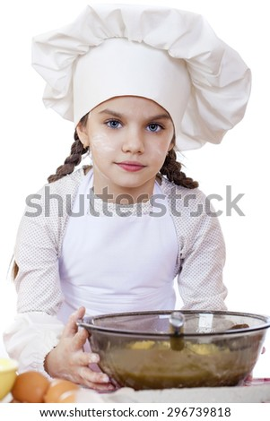 Portrait of a little girl in a white apron and chefs hat knead the dough in the kitchen, isolated on a white background - stock photo