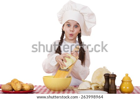Portrait of a little girl in a white apron and chefs hat shred cabbage in the kitchen, isolated on white background - stock photo