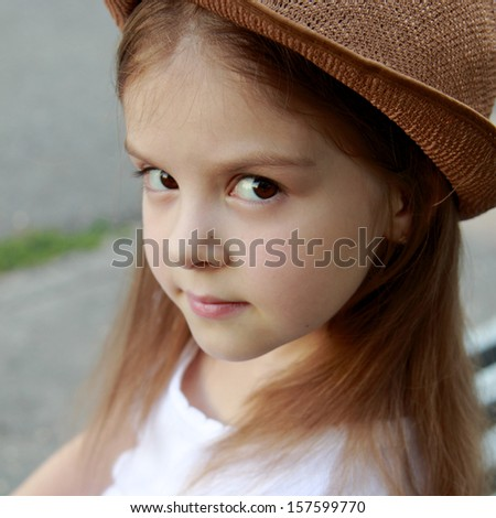 Portrait of a little girl in a white dress in a summer park sits on the bench in street - stock photo