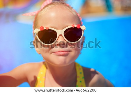 Portrait of a little girl in sunglasses near the accepted Swimming pool , which has a good time on summer vacations