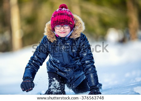 Portrait of a little girl in the snow. Winter joy of a child of a lot of snow.