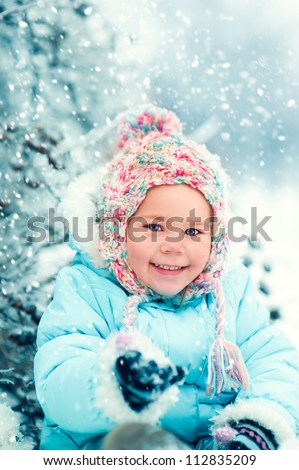 portrait of a little girl in winter clothes in snow forest at snowflakes background