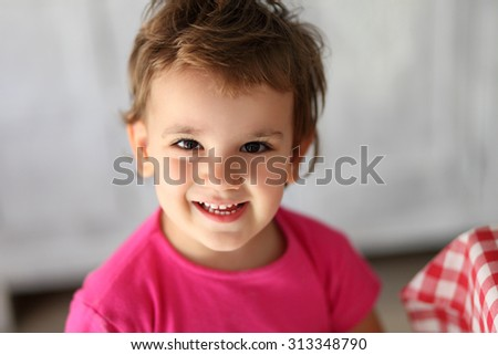 Portrait of a little girl looking and smiling at the camera - stock photo