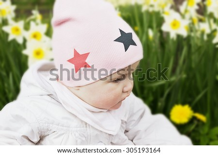 portrait of a little girl on a background of daffodils outdoors. carefree childhood.selective focus - stock photo