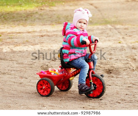 Portrait of a little girl on a bicycle in autumn  park outdoors