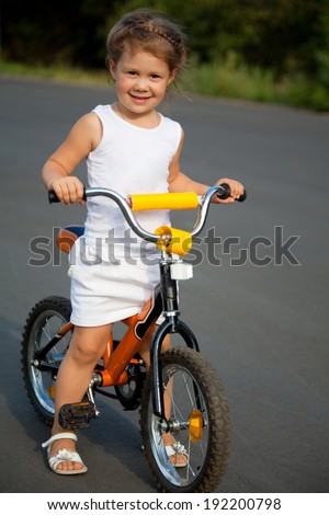 Portrait of a little girl on a bicycle in summer park outdoors  - stock photo