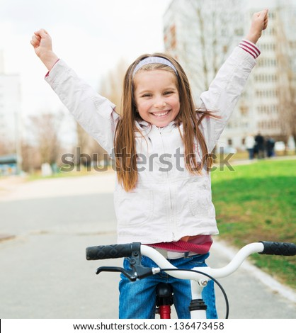 Portrait of a little girl on a bicycle with hands up - stock photo