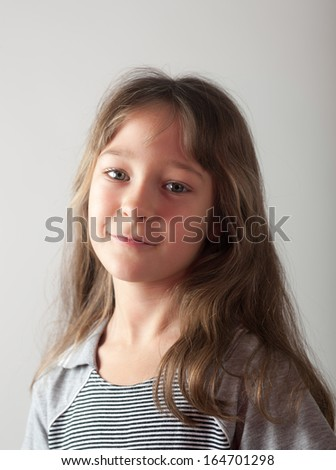 portrait of a little girl on a gray background