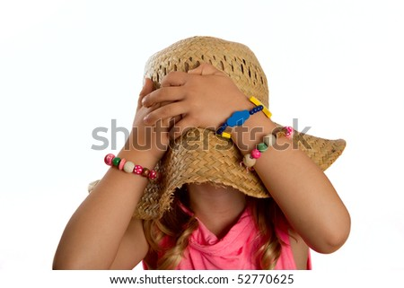 Portrait of a little girl pulling a straw hat over her head and hiding her face