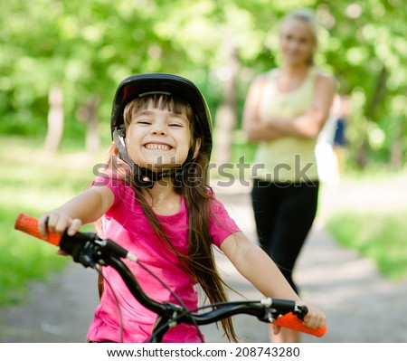 Portrait of a little girl riding her bike ahead of her mother - stock photo