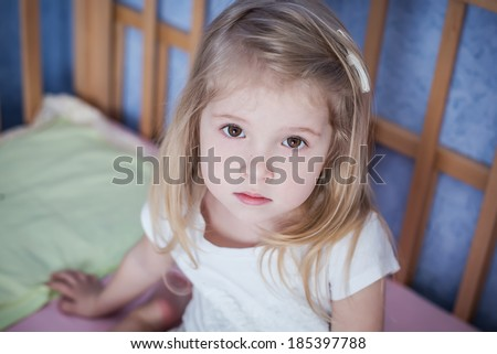 portrait of a little girl sitting in bed - stock photo