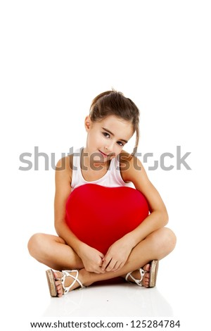 Portrait of a little girl sitting on floor and embracing a red balloon, isolated on white background - stock photo