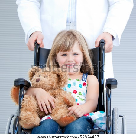 Portrait of a little girl sitting on the wheelchair supported by a male doctor at the hospital - stock photo