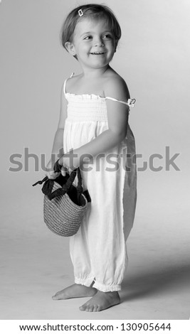 Portrait of a little girl standing smiling. - stock photo