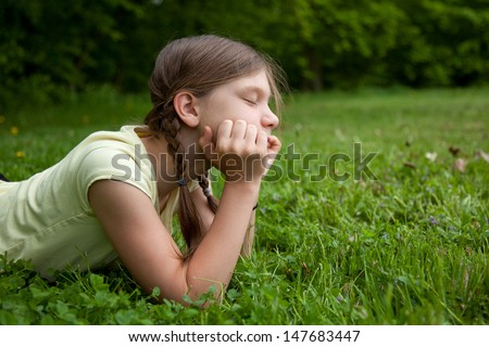 Portrait of a little girl thinking in a park on a green meadow