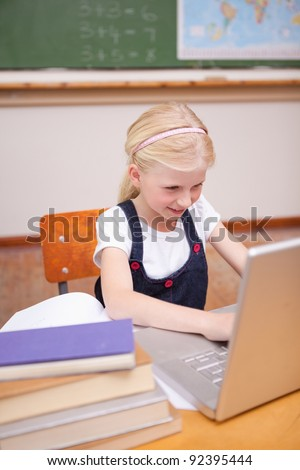 Portrait of a little girl using a laptop in a classroom