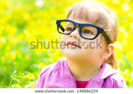 portrait of a little girl wearing glasses, outdoors - stock photo