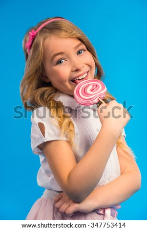 Portrait of a little girl with a big candy isolated on a blue background - stock photo