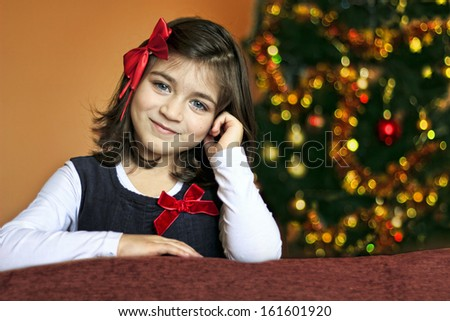 Portrait of a little girl with a red ribbon in front of Christmas tree - stock photo