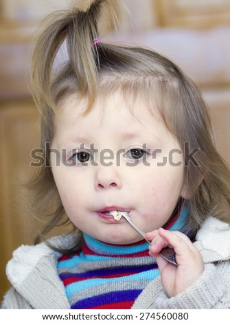 Portrait of a little girl with a spoon in the mouth
