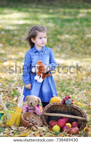 Portrait of a little girl with a toy dog in her hand in the park