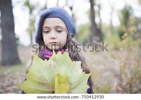 Portrait of a little girl with autumn leaves in the park