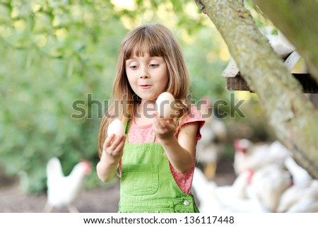 portrait of a little girl with eggs - stock photo