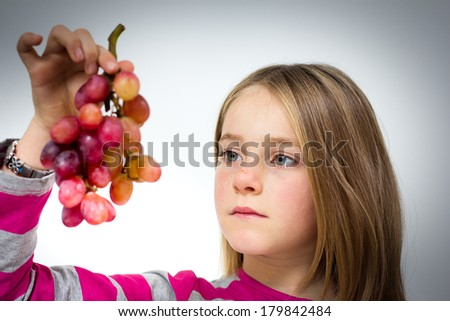 Portrait of a little girl with grapes - stock photo