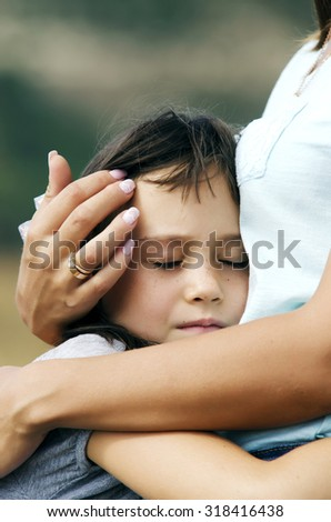 Portrait of a little girl with her eyes closed  hugging mother, outdoor - stock photo