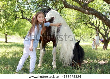 Portrait of a little girl with her favorite horse - stock photo
