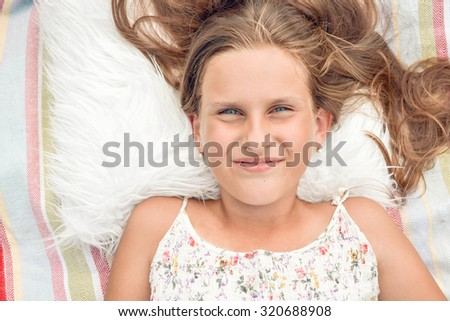Portrait of a little girl with long hair and blue eyes smiling  - stock photo