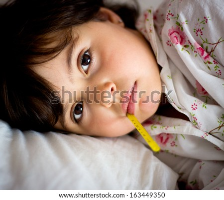 portrait of a little girl with thermometer in bed - stock photo