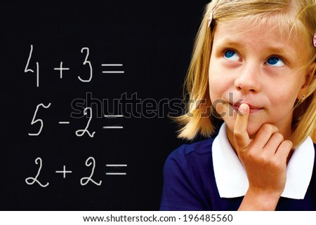 Portrait of a little happy pretty schoolgirl doing arithmetic on blackboard in class and smiling  - stock photo
