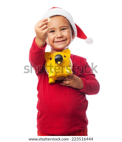 portrait of a little kid inserting coin in a piggy bank - stock photo