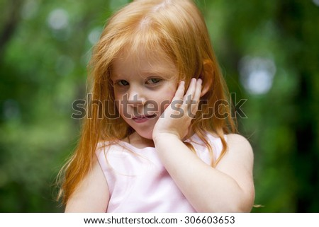 Portrait of a little red-haired girl on the background of summer green forest