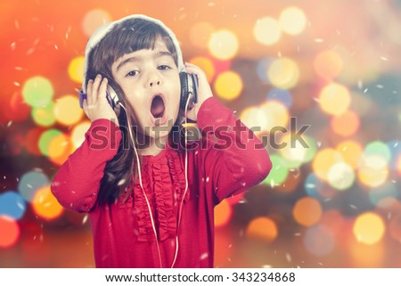 Portrait of a little Santa girl singing while listening to music. Defocused bokeh Christmas lights background. Cross processed image with shallow depth of field - stock photo